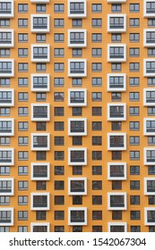 """New orange building facade in housing complex """"Salaryevo Park. PIK"""", Butovo, Moscow city, Russia. Modern style in architecture. House in dormitory area of Moscow. Urban subject. Symmetry in exterior"""