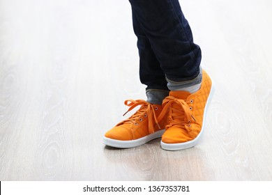 New orange sneakers with soft white soles closeup. Comfortable dance shoes. Legs of a girl dressed in jeans in a flirty pose isolated on light laminate. The first uncertain steps in a dance lesson