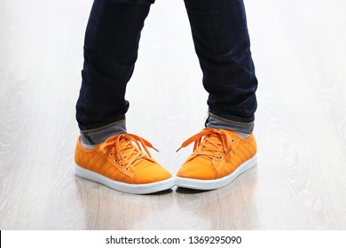 New orange sneakers with soft white soles closeup. Pigeon-toed foot position. Legs of a girl dressed in jeans in a clumsy pose isolated on light laminate. The first dance lesson of an unsure beginner