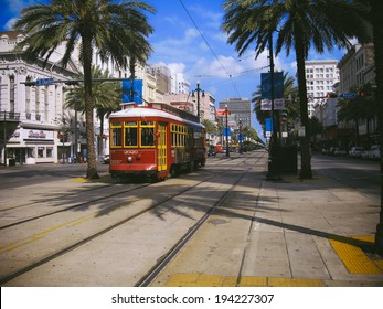 NEW ORLEANS - CIRCA JULY 2011: A streetcar among the palm trees lining Canal Street in New Orleans.
