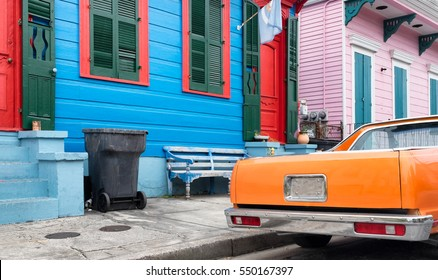 New Orleans colorful vintage painted houses and a classic orange car parked in front. Typical shotgun architectural style of homes seen in the historic neighborhoods.