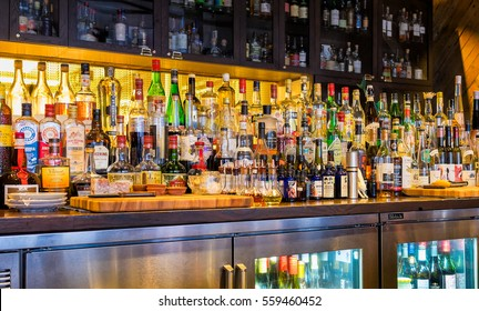 NEW ORLEANS - Dec. 25, 2016: Bar stocked with bottles of alcohol, spirits, and liqueurs. Variety of imported and domestic labels, brands and supplies for making cocktails and drinks.