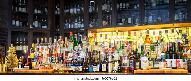 NEW ORLEANS- Dec.25, 2016: Bar stocked with bottles of alcohol, spirits, and liqueurs. Mix of imported and domestic labels, brands and supplies for cocktails and drinks. Wide shot viewed at an angle.