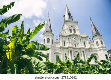 New Orleans famous church spires of the Cathedral Basilica of Saint Louis with banana palms under sunny blue sky in the French Quarter
