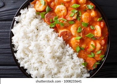 New Orleans gambo with shrimps and sausage close-up in a plate on the table. horizontal top view from above