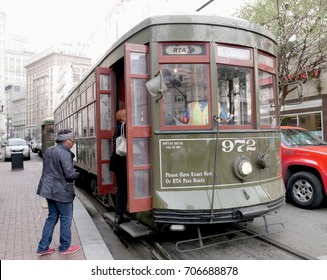 NEW ORLEANS, LOUISIANA—Passengers get on a green RTA Street Car line in New Orleans, Louisiana in January 2017. The street cars have wooden seats, open windows and no airconditioning units.