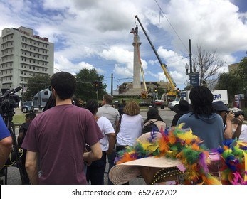NEW ORLEANS, LA CIRCA MAY 19 2017 - crowd of African American and Caucasian people watch construction crew attach a crane and prepare to remove confederate monument symbol General Robert E Lee statue