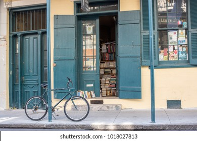New Orleans, LA, January 23, 2018: Beautiful scene in the French Quarter - A bicycle is parked outside a booktore with books lined on shelves at the window. Typical architecture for the French Quarter