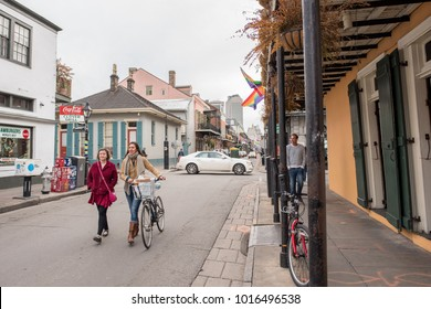 New Orleans, LA, January 24, 2018: Two young women friends walk and talk along the street in the French Quarter. The city attracts as many as ten million visitors yearly, and is very bicycle friendly.