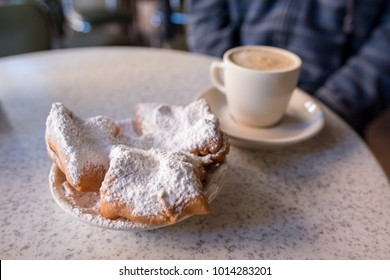 New Orleans, LA, January 25, 2018: Beignets covered with powdered sugar, served with cafe au lait at the famous Cafe Du Monde in the French Quarter. Shallow focus on the powdered sugar for effect.