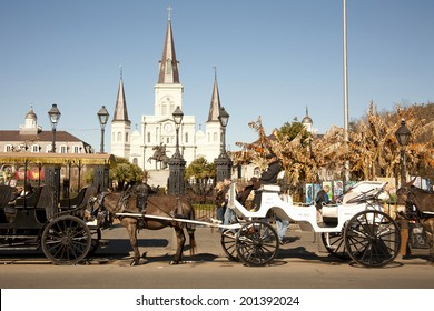 New Orleans, LA, USA - January 24, 2011 : Tourists and artists pass the mule drawn carriages in front of Jackson Square and the St Louis Cathedral in New Orleans Louisiana