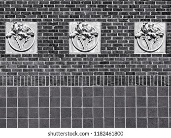 New Orleans, LA USA - May 9, 2018  -  Concrete 3 Flowers on Red Brick Wall at Tulane University B&W