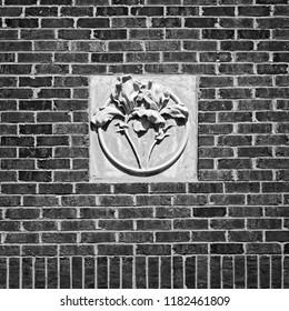 New Orleans, LA USA - May 9, 2018  -  Concrete Flower on Red Brick Wall Tulane University B&W