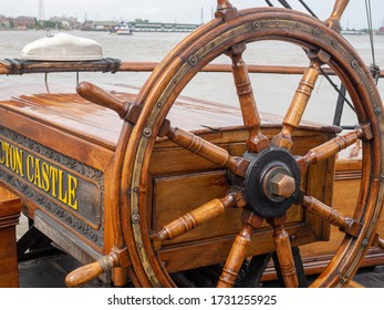New Orleans, LA/USA - 4/21/2018: Steering Wheel on Tall Ship Picton Castle Docked in Mississippi River by Woldenberg Park with Tugboat and Wharves in Background