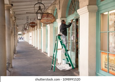 New Orleans, Louisiana - 12/14/2011: a painter is hard a work painting the door and trim of shops in a downtown New Oreleans business district.