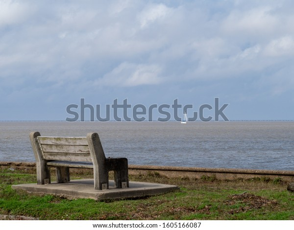 New Orleans, Louisiana: Bench on lake Pontchartrain with Sailboat in Background Intentionally Out of Focus