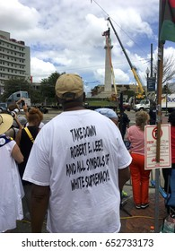 "NEW ORLEANS, LOUISIANA CIRCA MAY 19, 2017 - African American Activist watches removal of confederate General Lee Statue. His t-shirt says ""Take down Robert E Lee and all symbols of white supremacy""."