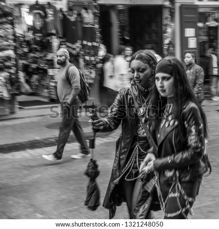 New Orleans, Louisiana - December 30, 2018: People stroll along Bourbon Street, in the French Quarter, including a woman checking her phone while walking, over the new year's eve weekend.