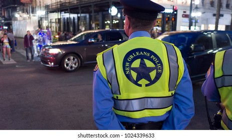 NEW ORLEANS, LOUISIANA - FEBRUARY 9, 2018 - Local police officer standing guard along Hermes Parade route for Mardi Gras celebration on February 9, 2018 in New Orleans, Louisiana.