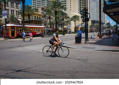 New Orleans, Louisiana - June 18, 2014: Street scene at Canal Street with a man on a bicycle in the downtown of the city of New Orleans, Louisiana, USA