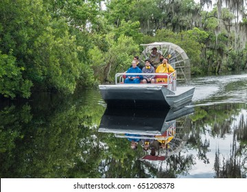 New Orleans, Louisiana - May 22, 2017; A group of people take an airboat swamp tour, a popular attraction of tourists to the area to enjoy the scenery and wildlife, including numerous alligators.