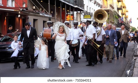 NEW ORLEANS, LOUISIANA - MAY 5th: Bride and groom lead wedding parade down the streets of the historic French Quarter in New Orleans, Louisiana on May 5th, 2016.