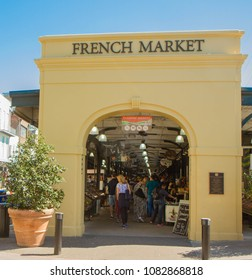 New Orleans, Louisiana, United States - March 31, 2018: French Market Arch in French Quarter of New Orelans, Louisiana, USA. Arch is canary yellow color and has people and shops visible inside market.