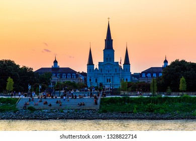 NEW ORLEANS, LOUISIANA / USA - 25 AUGUST, 2018 : Tourists on the waterfront in front of  the Saint Louis Cathedral and Jackson Square during sunset time