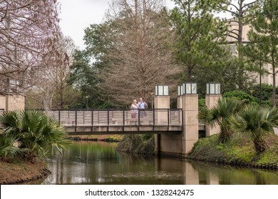 New Orleans, Louisiana / USA - February 16, 2019: People crossing a beautiful bridge over a pond in the scenic Sculpture Garden outside the New Orleans Museum of Art (NOMA).