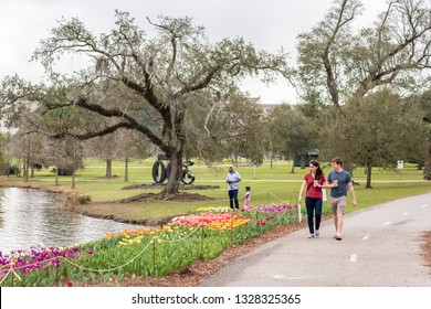 New Orleans, Louisiana / USA - February 16, 2019: People walking and enjoying the day at the beautiful City Park, which contains gardens, ponds and miles of walking trails.