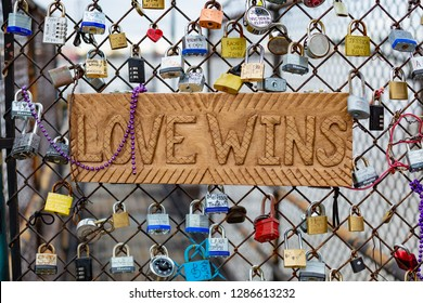 "NEW ORLEANS, LOUISIANA / USA - JANUARY 13, 2019: Love locks and sign ""Love Wins"" by the Mississippi River in the French Quarter of New Orleans symbolizing everlasting love."