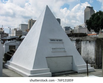 New Orleans, Louisiana, USA - June 16, 2012: A pyramid-shaped mausoleum in historic St. Louis Cemetery with the skyline of the city in the background. Latin inscription means All From One.