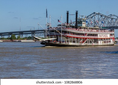 New Orleans, Louisiana, USA - March 31, 2018: Natchez steamboat cruising in front of bridge on Mississippi River. Late afternoon light, blue sky, people can be seen on boat, horizontal, blue sky.