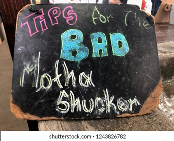 "New Orleans, Louisiana USA / October 15, 2018: worn sign "" Tips for the Bad Motha Shucker""  humorous take on tipping the oyster shucker in the restaurant"