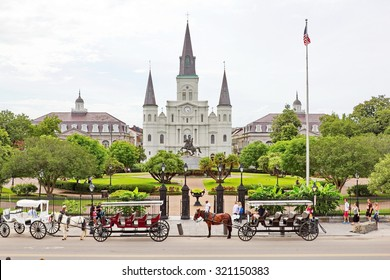 NEW ORLEANS, MISSISSIPPI, USA - MAY 26, 2015: Tourists mingle in Jackson Square, New Orleans, St. Louis Cathedral visible; horse and carriages wait to take people on tours of New Orleans in May 2015.