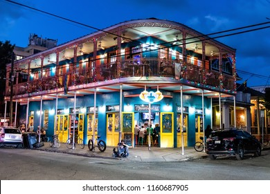 New Orleans, USA - April 22, 2018: Restaurant Dat Dog selling hot dogs with people sitting, eating, beggars on street, night road, evening, blue hour dusk, twilight, illuminated lights, illuminations