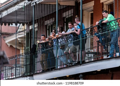 New Orleans, USA - April 22, 2018: Old town Bourbon street in Louisiana town, city, cast iron balcony building, party people standing by restaurant outdoor bar drinking beer during evening sunset