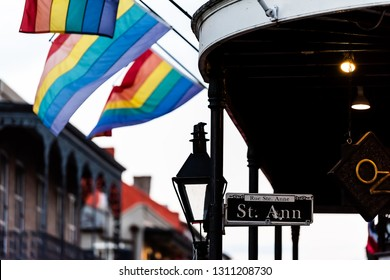 New Orleans, USA - April 22, 2018: Old town Bourbon street in Louisiana town city with Saint Ann building party nightlife by restaurant outdoor bar in dark evening with lgbt flags