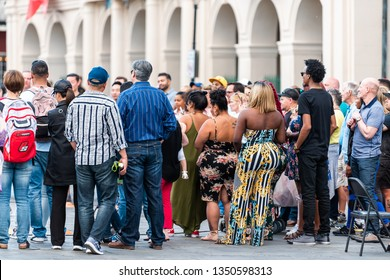 New Orleans, USA - April 22, 2018: Downtown skyline old town chartres street in Louisiana famous town city with many people crowd on Jackson square watching performance
