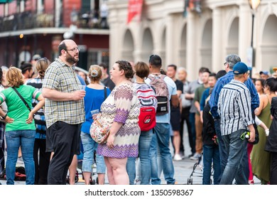 New Orleans, USA - April 22, 2018: Old town chartres street in Louisiana famous town city with many people crowd on Jackson square drinking alcohol from plastic cups