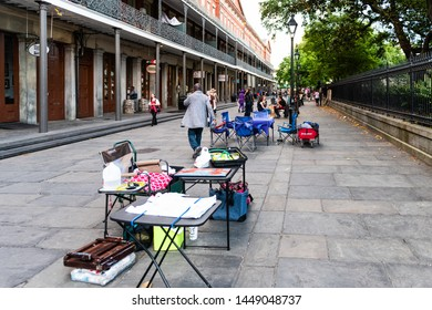 New Orleans, USA - April 22, 2018: St Peter street by Jackson Square with psychic tarot card reading palm woman by tables and chairs, people walking in summer