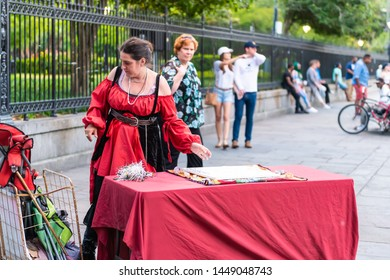 New Orleans, USA - April 22, 2018: Psychic tarot card reading palm woman in red dress costume on St Peter street by Jackson Square, people walking in summer