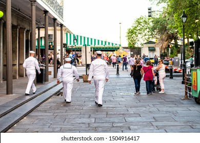 New Orleans, USA - April 22, 2018: Group of sailors, people men walking on street by Jackson square with Cafe Du Monde in blurred background in Lousiana old town city