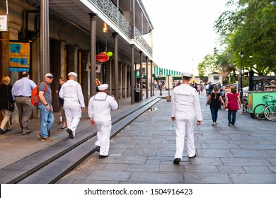 New Orleans, USA - April 22, 2018: Group of sailors men back walking on street by Jackson square with people in blurred background in Lousiana old town city by stores