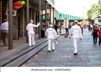 New Orleans, USA - April 22, 2018: Group of sailors men walking on street by Jackson square with people in blurred background in Lousiana old town city by stores