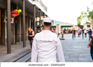 New Orleans, USA - April 22, 2018: Closeup of one sailor man back walking on street by Jackson square with people in blurred background in Lousiana old town city