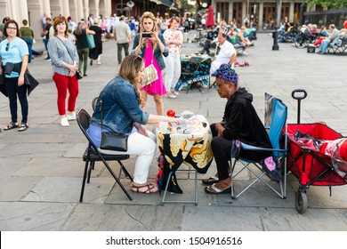 New Orleans, USA - April 22, 2018: Old town street in Louisiana town city by St Louis cathedral church and many people crowd on Jackson square with tarot card reading palm woman