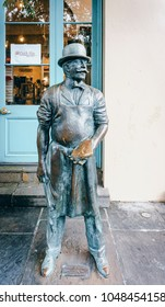New Orleans, USA - Aug 20, 2017: At the Dutch Alley Artist's Co-op (French Quarter). Front life-size bronze statue is Jacques the Butcher by Eric Kaposta. Artists are also sales people in this co-op.