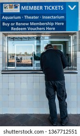 New Orleans, USA - Dec 10, 2017: At the ticket booth to the popular Audubon Aquarium of the Americas. A man at the booth in the process of purchasing a ticket.