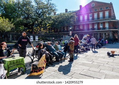 New Orleans, USA - Dec 11, 2017: Crowds relaxing in the sun along park benches, including some street entertainers. Image captured at the iconic French Quarter, in front of Jackson Square.
